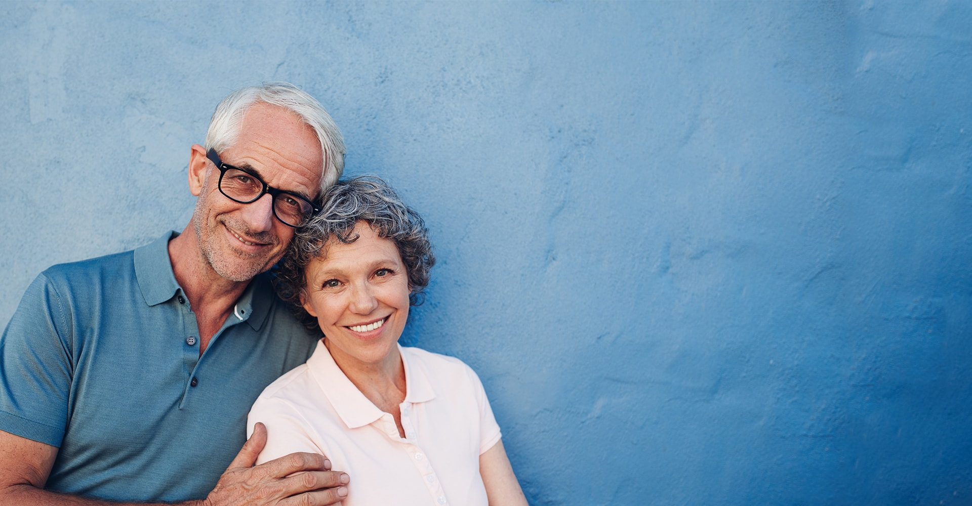 An older couple leaning against a blue wall smiling to show how dental implants from our Bellevue dentist can transform your smile