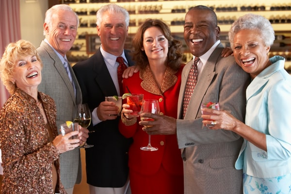 Photo mixed group of older friends smiling at a party showing how do dental implants work to restore your confidence and self-esteem
